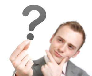 Man in a grey suit holding a question mark and thinking about selling his alarm company