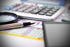 calculator, pen and other materials for calculating the value of a business before a sale
