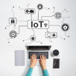 IoT security theme with person using a laptop