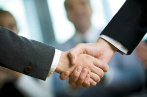 Close up of handshake between two businessmen after an alarm company purchase