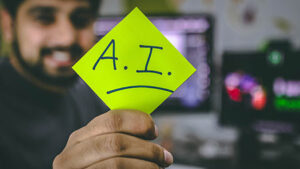 alarm system monitoring employee holding a yellow post it note that says A.I.