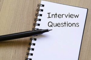 a pen with a notebook that says 'interview questions'