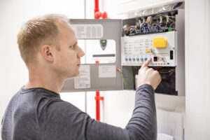 Technician looking at fire alarm panel
