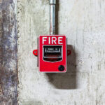 Fire alarm push button equipment in old factory representing the concept of a fire integration company